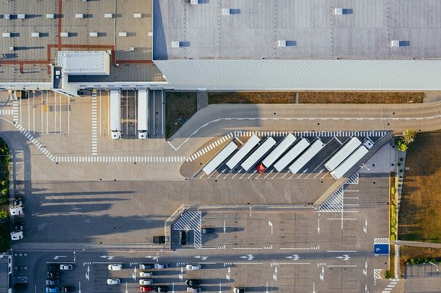 An aerial view of parking with multiple trucks carrying shipping containers.